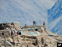 FILE - This photograph provided by the Indian Army, shows Chinese troops dismantling their bunkers in the Pangong Tso region, in Ladakh along the India-China border, Feb.15, 2021.
