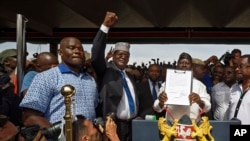 "FILE - opposition politician Miguna Miguna, center, raises his fist as a gesture to the crowd as he stands next to opposition leader Raila Odinga, center-right, and politician James Orengo, far right, as Odinga holds an oath during a mock ""swearing-in"" ceremony at Uhuru Park in downtown Nairobi, Kenya, Jan. 30, 2018."