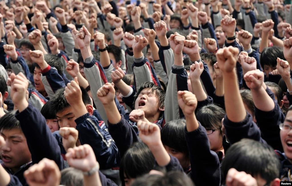 """2012年3月28日,江蘇省南京市一所高中的學生聽勵志演講時,跟著講演者喊出""""我必須上大學""""和""""爸爸媽媽我愛你""""等口號。"""