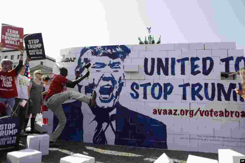 Protestors tear down a so-called 'Trump's wall of hate' as part of a demonstration against U.S. Republican presidential candidate Donald Trump in front of the Brandenburg Gate at the Pariser Platz in Berlin, Germany.