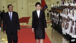 លោក ហ៊ុន សែន នាយករដ្ឋមន្ត្រីកម្ពុជា (ឆ្វេង) និងសមភាគីថៃ គឺ លោកស្រី យីងឡាក់ ស៊ីណាវ៉ាត្រ (Yingluck Shinawatra) (កណ្តាល) ក្នុងពិធីត្រួតពលនៅវិមានសន្តិភាពក្រុងភ្នំពេញ កាលពីថ្ងៃព្រហស្បតិ៍ទី១៥ខែកញ្ញាឆ្នាំ២០១១នេះ។