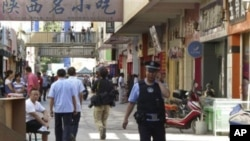 2011年8月2日一名巡逻的警察在之前不久在喀什发生袭击地点附近的大街上用手机打电话