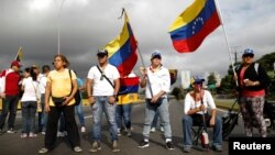 Opposition supporters wave Venezuelan national flags while blocking a highway to protest President Nicolas Maduro's government, in Caracas, May 15, 2017.