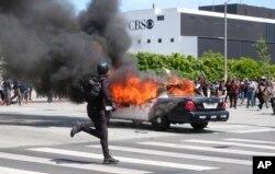 Una persona corre mientras un vehículo de la policía arde durante una protesta por la muerte de George Floyd. Los Angeles, mayo 30 de 2020.