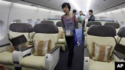 Visitors walk inside the cabin of a scale model of a Chinese-made C919 passenger airliner at the 8th China International Aviation and Aerospace Exhibition (Zhuhai Airshow) in Zhuhai, southern coast of Guangdong province, China, 16 Nov 2010.