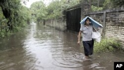 A woman walks through floodwaters after heavy rains in La Libertada October 19, 2011. The death toll from torrential rains in Central America over the past week has almost doubled since Saturday, with a further 32 lives lost in El Salvador, authorities sa