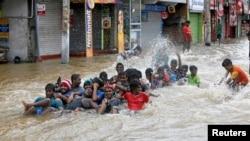 Un groupe de personnes jouant sur une route inondée après fui leurs maisons à Biyagama, Sri Lanka, 17 mai 2016.