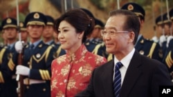 Chinese Premier Wen Jiabao, right, shows the way to Thai Prime Minister Yingluck Shinawatra as during a welcome ceremony for her at the Great Hall of the People in Beijing, China, April 17, 2012.