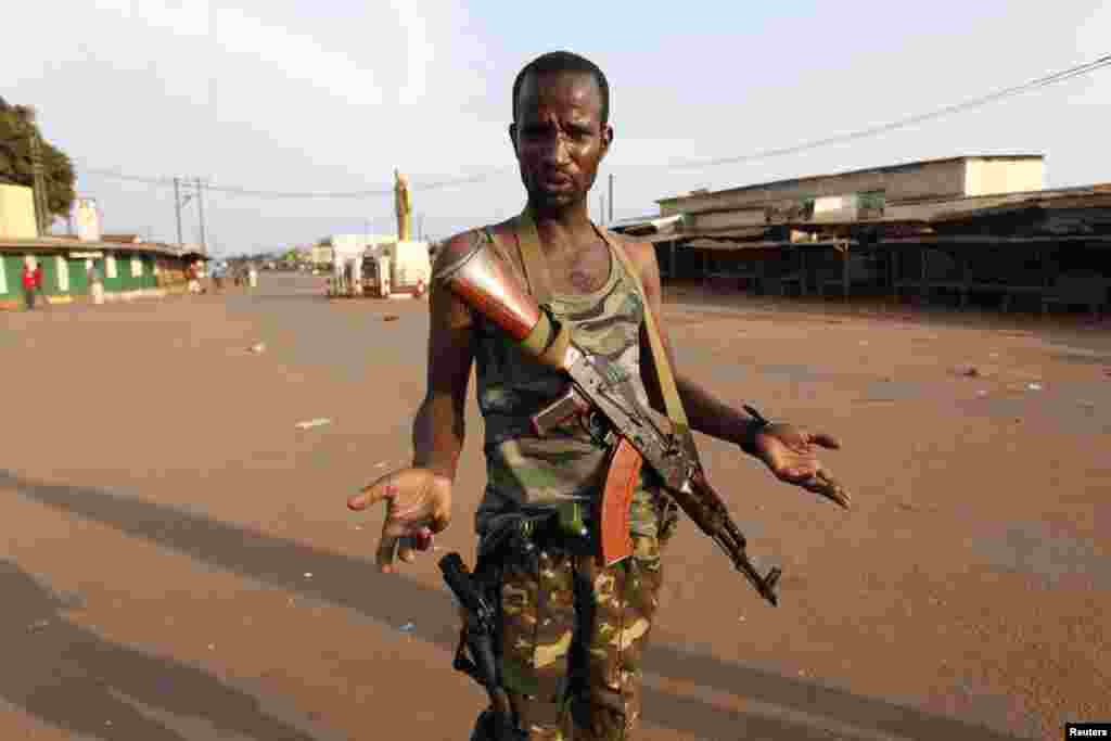 A Seleka fighter gestures outside a mosque where bodies of people killed during fighting are gathered in Bangui, Central African Republic, Dec. 5, 2013.