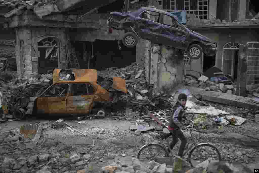 ក្មេងប្រុសម្នាក់ជិះកង់កាត់រថយន្ត និងផ្ទះ នៅក្នុងសង្កាត់មួយដែលថ្មីៗនេះវាយដណ្តើមដោយកងកម្លាំងអ៊ីរ៉ាក់ នៅភាគខាងលិចនៃក្រុង Mosul។