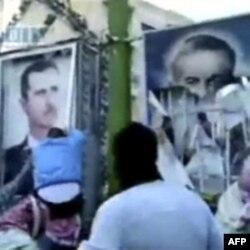 Demonstranti uklanjaju postere sa likom sirijskog predsednika