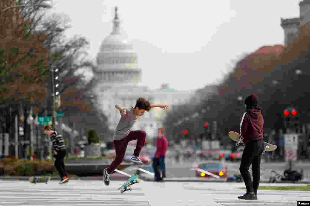 Children perform skateboard tricks at Freedom Plaza as Mayor Muriel Bowser declared a state of emergency due to the coronavirus outbreak (COVID-19) in Washington, D.C., March 16, 2020.