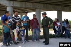 边境巡逻人员在德克萨斯州同从墨西哥非法越境进入美国的人交谈。(2018年4月2日)