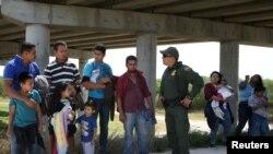 2018年4月2日,德克萨斯州麦卡伦附近的格兰德谷地区,边境巡逻员吉奥拉米雷斯与非法从墨西哥越境进入美国的移民进行对话。