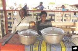 Two women vendors sell bush meat stews at market near Yaounde, Cameroon