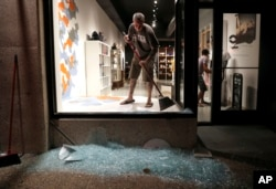 Scott McRoberts helps clean up broken glass after a violent crowd broke windows of many businesses after clashing with police, Sept. 16, 2017, in University City, Mo. Earlier, protesters marched peacefully in response to a not guilty verdict in the trial