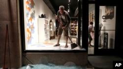 圣路易斯郊区一家高档店的玻璃被示威者打碎,图中男子正在清算碎玻璃。