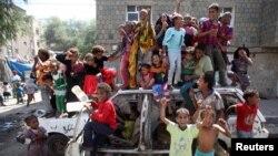 Anak-anak bermain di sebuah mobil yang rusak pasca kerusuhan di negara itu antara pemerintah dan milisi Muslim Syiah Houti, di kota Taiz, Yaman (13/2).
