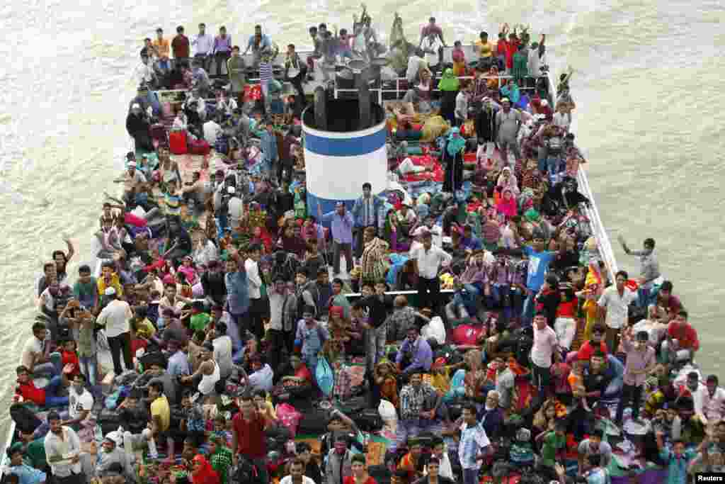 People look on from an overcrowded passenger boat navigating through the Buriganga River in Dhaka, Bangladesh.