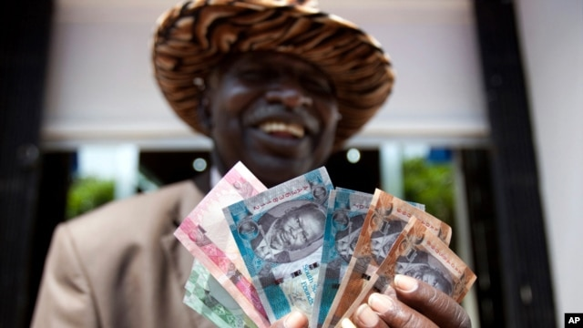 July 19: A man from South Sudan displays new currency notes outside the Central Bank of South Sudan in Juba. REUTERS/Benedicte Desrus