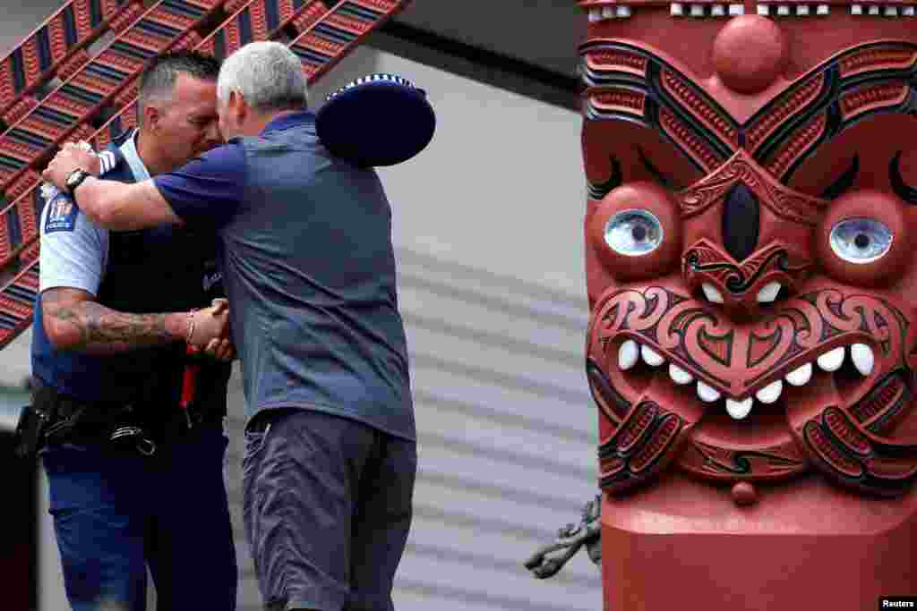 "A police officer and a man perform a Hongi after a ceremony called ""Karakia"", attended by Ngati Awa representatives and relatives of the volcano eruption victims at Mataatua Marae house in Whakatane, New Zealand."
