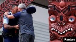 "Seorang petugas polisi dan seorang pria melakukan ritual Hongi setelah upacara ""Karakia"", yang dihadiri perwakilan Ngati Awa dan kerabat korban letusan gunung berapi, di rumah Mataatua Marae, Whakatane, Selandia Baru, 12 Desember 2019."