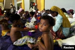 A child, believed to be Rohingya, eats inside a shelter after he was rescued along with hundreds of others on Sunday from boats in Lhoksukon, Indonesia's Aceh Province, May 12, 2015.