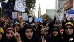 Niñas estudiantes iraníes hace el signo de la victoria en una manifestación anual frente a la excede de la embajada de EE.UU. en Teherán, en el aniversario de la toma de la sede diplomática el sábado, 4 de noviembre de 2017.