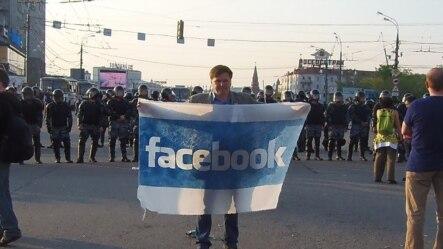 2012年5月6日普京再次就任总统前夕,莫斯科市中心爆发大规模反政府示威,一名示威者手举脸书旗帜。(美国之音白桦拍摄)