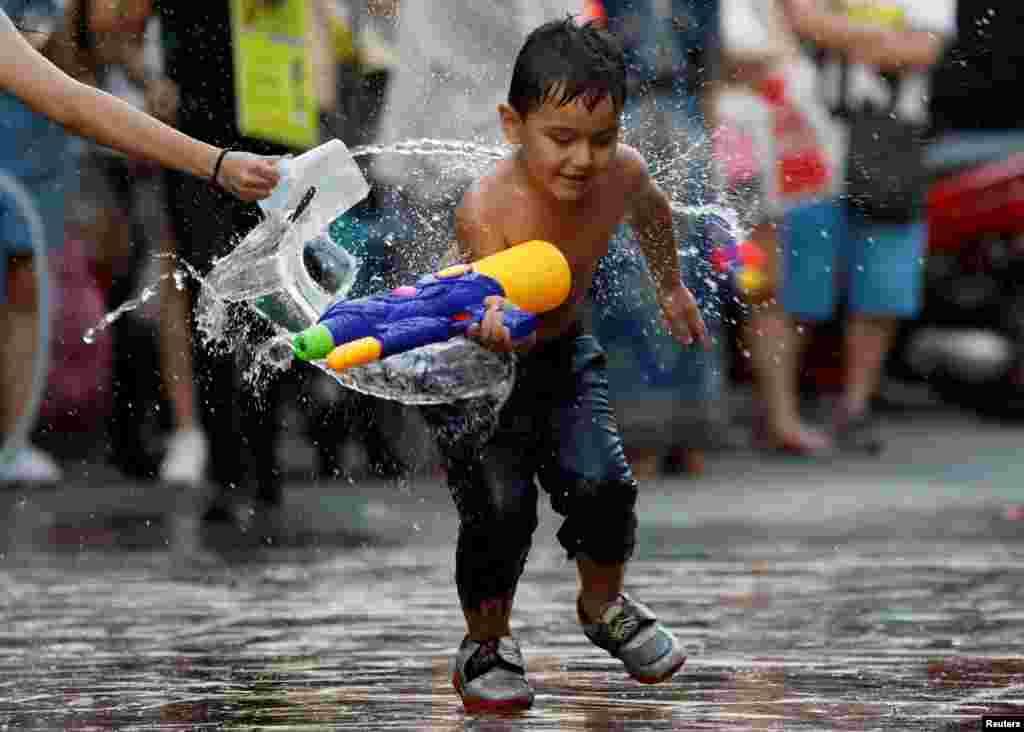"Dečak se igra sa vodom tokom proslave festivala vode ""Songkran"" u znak obelavanja Nove Godinena Tajlandu."