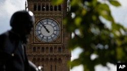 The statue of former British Prime Minister David Lloyd George is silhouetted against the Queen Elizabeth Tower which holds the bell known as 'Big Ben' in London, Monday, Aug. 14, 2017.