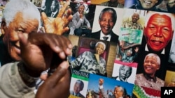 A well-wisher uses his phone to take a picture of a banner of photos of Nelson Mandela, outside the Mediclinic Heart Hospital in Pretoria, July 18, 2013.