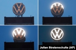 In this Monday, September 9, 2019 combiantion of four photos workers unveil the new company logo of the German car manufacturer 'Volkswagen' on top of the company's headquarters in Wolfsburg, Germany.