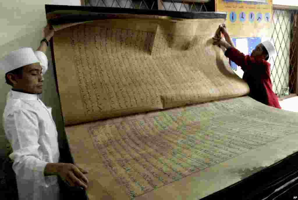 Teachers show a giant Quran displayed at Al-Ashriyyah Nurul Iman boarding school in Parung, West Java, Indonesia.