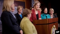 Sen. Elizabeth Warren, D-Mass., center, accompanied by fellow Democratic Women Senators, speaks during a news conference on Capitol Hill in Washington, Jan. 30, 2014, to show their support on raising the federal minimum wage.