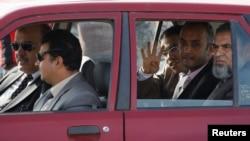 穆斯林兄弟会及被推翻的总统穆尔西的律师乘车抵达审判现场并打出手势。(2013年11月4日)