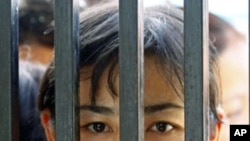Family members of prisoners wait for their release in front of the Insein Prison gate in Yangon. Myanmar's new government began freeing about 14,000 prisoners and commuting thousands more sentences on Tuesday in an amnesty critics dismissed as a token ges