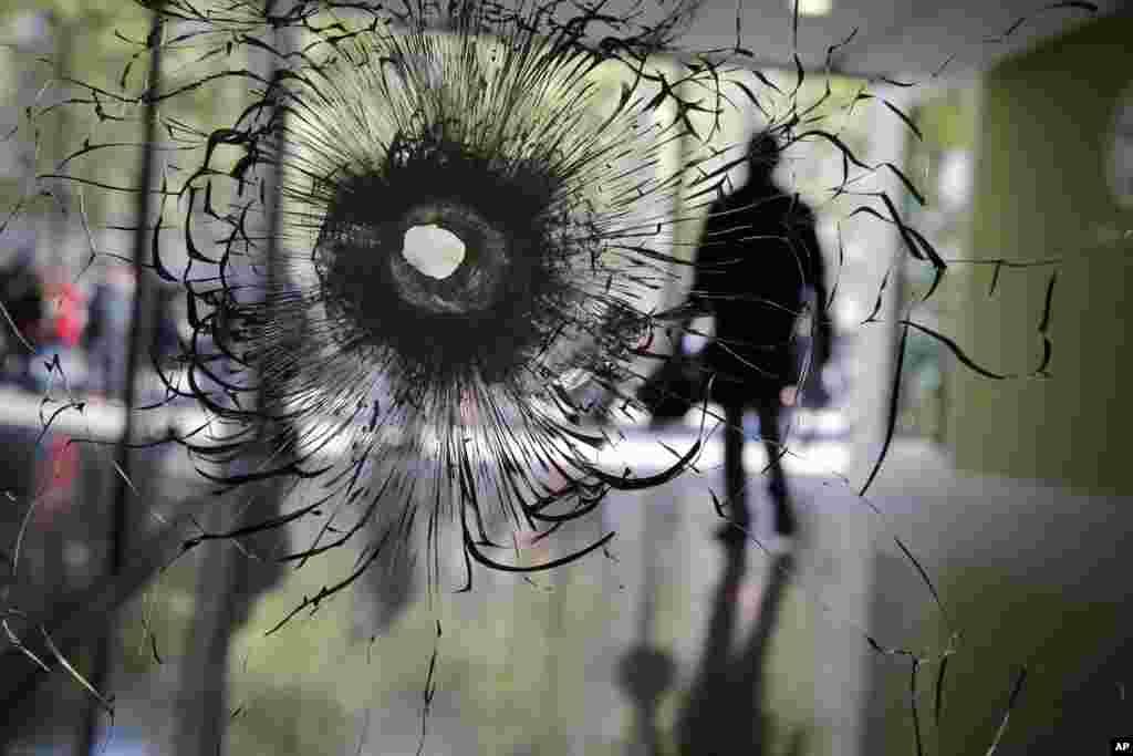 سوراخ ایجاد شده بر روی ویترین مغازه ای در شانزلیزه فرانسه در اثر اصابت با گلوله