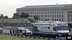 Law enforcement work near the Pentagon after a suspicious vehicle forced multiple road closures, June 17, 2011 in Arlington, Va.