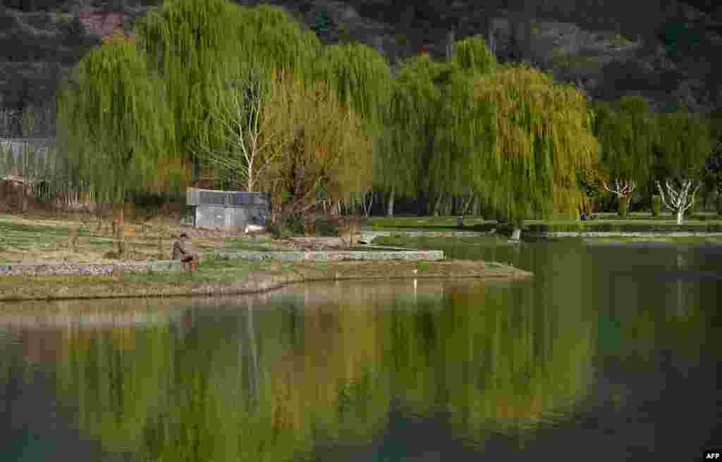 An Indian Kashmiri man sits by a lake in a garden by the Zabarwan Hills in Srinagar.