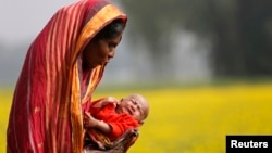 Monowara holds her 22-day-old grandson Arafat, as she walks through a mustard field on the outskirts of Dhaka, Bangladesh, Jan. 22, 2014.