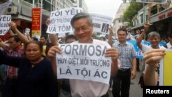"FILE - Political dissident Nguyen Quang A (C) holds a sign which reads ""Formasa - damaged the environment and is a criminal"" during a protest in Hanoi, Vietnam, May 1, 2016."