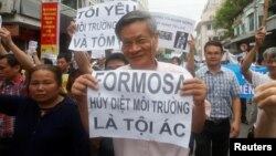 "Political dissident Nguyen Quang holds a sign which reads ""Formosa - damaged the environment and is a criminal"" during a protest in Hanoi, Vietnam May 1, 2016 against a unit of Taiwan's Formosa Plastics."