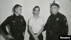 Звинувачений у вбивстві президента Кеннеді Лі Гарві Освальд в оточенні поліцейських