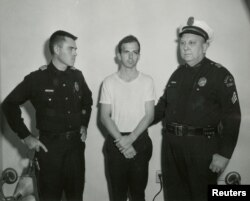 FILE - Lee Harvey Oswald, accused of assassinating U.S. President John F. Kennedy, is pictured with a Dallas police sergeant and an officer in this handout image taken Nov. 22, 1963.