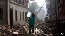 FILE - A Nepalese man carrying a water jar walks past damaged houses in Bhaktapur, Nepal, May 14, 2015.