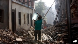 A Nepalese man carrying a water jar walks past damaged houses in Bhaktapur, Nepal, May 14, 2015.