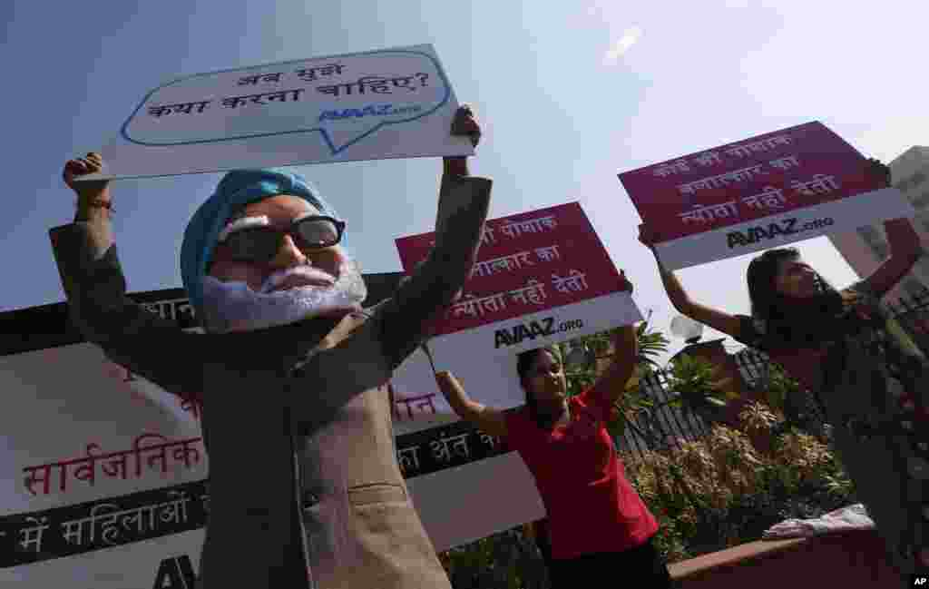 A man wearing a mask of Indian Prime Minister Manmohan Singh participates in a protest along with women outside the court where the accused in the gang rape will be tried, in New Delhi, India, January 21, 2013.