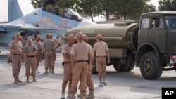 FILE - Russian air force personnel stand near a Russian war plane at Hmeymim airbase, Syria, Oct. 22, 2015.