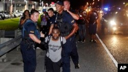 FILE - In this July 9, 2016 photo, police officers arrest activist DeRay McKesson during a protest along Airline Highway, a major road that passes in front of the Baton Rouge Police Department headquarters in Baton Rouge, La., after the fatal shooting of